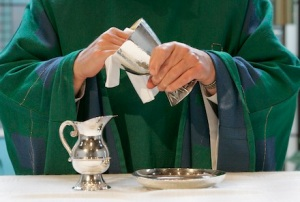 A photo illustration shows a priest cleaning the Communion vessels inside the chapel of the U.S. Conference of Catholic Bishops' building in Washington Oct. 24. At the direction of Pope Benedict XVI, extraordinary ministers of holy Communion will no longer be permitted to assist in the purification of the sacred vessels at Masses in the United States. (CNS photo illustration/Bob Roller) (Oct. 24, 2006) See SKYLSTAD-VESSELS Oct. 24, 2006.